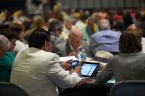 The Rev. Eradio Valverde Jr., from the Southwest Texas (regional) Conference, multi-tasks while listening to May 4 plenary session at 2012 United Methodist General Conference in Tampa, Florida. Photo by Kathleen Barry, UMNS.