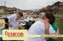 Homeowner Connie Boevers (right) is comforted by the Rev. Tish Malloy after a tornado swept through Boevers neighborhood in Oklahoma City in 2013. At left is the Rev. Adam Shahan. Malloy is pastor of First United Methodist Church in Moore, Okla. Photo by Mike DuBose, UMNS.