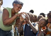 Sharlene Jean offers a sample of treated drinking water to a child living in a makeshift camp in Gresier, Haiti. Photo by Mike DuBose, UMNS.
