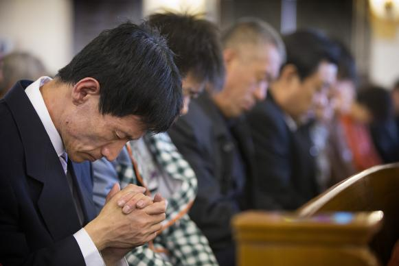 Parishioners pray during worship at Chongwenmen Church Beijing, China in 2013. The United Methodist Board of Global Ministries had named a new China Program associate, Liu Ruhong to work with the denomation's partners in China and the region. Photo by Mike DuBose, UMNS.