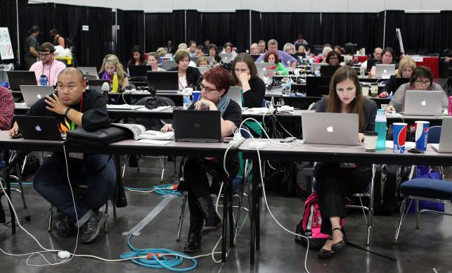 The newsroom of the 2016 United Methodist General Conference in Portland, Ore. is a busy place with journalists covering sessions. In the center is Kathy L. Gilbert, reporter for United Methodist News Service. Photo by Kathleen Barry, United Methodist Communications.