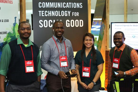 (From left) Chilima Karima, Joe Tueche Ndzulo, April Mercado and Pierre Omadjela stand in the ICT4D booth for United Methodist Communications. Photo by Kathleen Barry, United Methodist Communications.