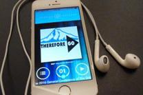 """A smart phone displays the logo """"Therefore Go"""" used for the United Methodist General Conference 2016. The headphones and app will provide a """"hearing hotspot"""" for translation into different languages. Photo by Greg Nelson, United Methodist Communications. Cropped from original."""