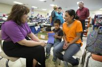 United Methodist Bishop Minerva Carcaño (left) visits with Regino Enrique, 5, and his mother, Macaria, at the immigrant welcome center at Sacred Heart Catholic Church in McAllen, Texas. Photo by Mike DuBose, UMNS.