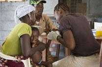 Health worker Juliana Koroma (right) takes a blood sample from Issata Jusu for a malaria test at the Koribondo Community Health Center near Bo, Sierra Leone. Holding the child is her is her mother, Umu Koroma. At rear is health worker Ishmael Karoma. Photo by Mike DuBose, UMNS