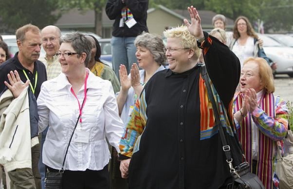The Rev. Amy DeLong (right front) and her partner Val Zellmer wave to supporters as they enter Peace United Methodist Church in Kaukauna, Wis., on the third day of DeLong's United Methodist Church trial on charges she violated the church's rules on sexuality. A UMNS photo by Mike DuBose.