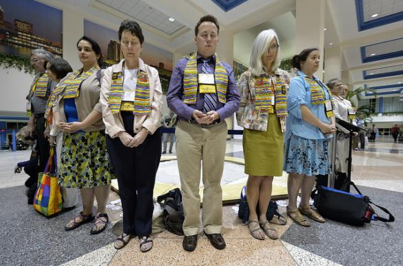 Outside the plenary session of the 2012 United Methodist General Conference in Tampa, Florida, supporters of full inclusion of gays and lesbians in the life of the church hold a silent vigil as delegates and visitors leave an April 26 session. A UMNS photo by Paul Jeffrey.