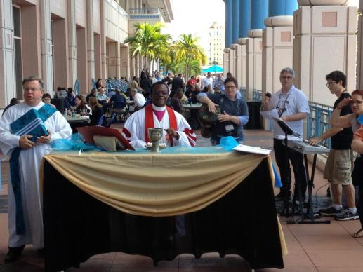 Bishop John Innis presides at noon-day Communion Service on the Riverwalk