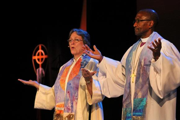 Bishops Deborah Lieder Kiesey and Marcus Matthews raise their hands in prayer during the May 3 evening music at the 2012 United Methodist General Conference in Tampa, Fla. is decorated in deep red. A UMNS photo by Kathleen Barry