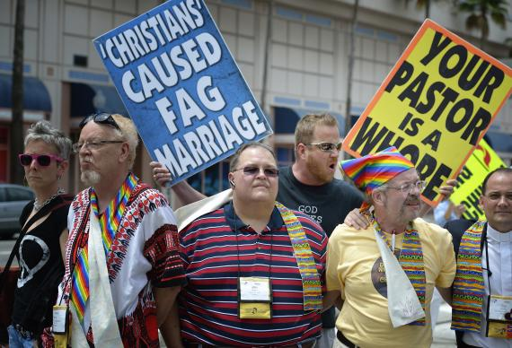 United Methodist activists form a human shield to block a demonstrator from the Westboro Baptist Church on May 4 outside the 2012 United Methodist General Conference in Tampa, Florida. The United Methodists belong to a group that supports the full inclusion of gays and lesbians in the life of the church, while the Westboro demonstrators travel widely with their anti-homosexual agenda. A UMNS photo by Paul Jeffrey.