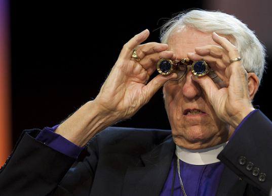 Bishop William Boyd Grove uses opera glasses to view a delegate speaking at a distant microphone during the 2012 United Methodist General Conference in Tampa, Fla. A UMNS photo by Mike DuBose.