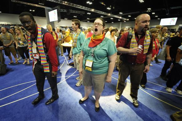 Protestors take over the floor at the end of a May 2 session of the 2012 United Methodist General Conference in Tampa, Fla. They expressed concern that the church's decisions on restructure, ending guaranteed clergy appointments, human sexuality and corporate divestment were made without hearing the voice of youth and others in the church. The protestors sang and chanted as the presiding bishop gave a closing prayer. A UMNS photo by Paul Jeffrey.