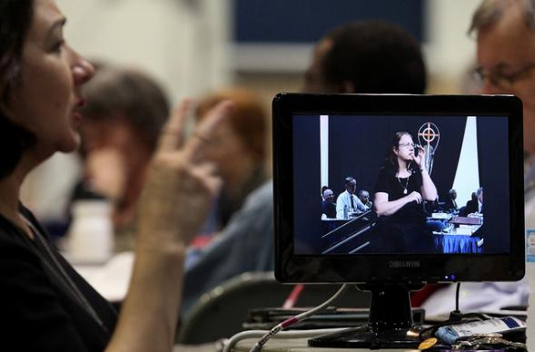 Michelle Provart Menefee works as a sign language interpreter on May 2 during the 2012 United Methodist General Conference in Tampa, Fla. Next to her is a monitor showing the signing from another part of the plenary area. A UMNS photo by Kathleen Barry