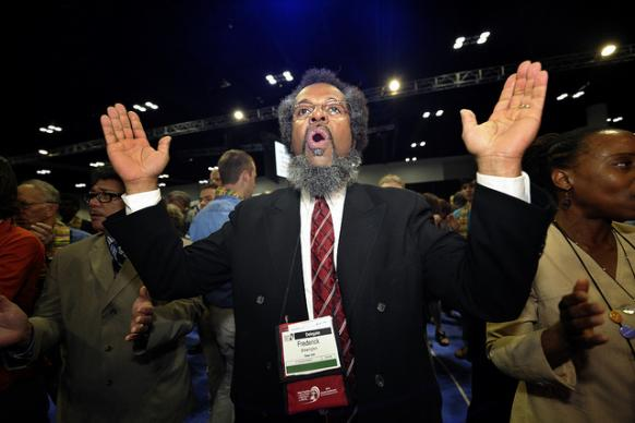 Frederick Brewington, a delegate from the New York annual conference, was among dozens of demonstrators demanding a more inclusive church who took over the floor of a May 3 session of the 2012 United Methodist General Conference in Tampa, Florida. They held communion around the center table and sang songs. Several remained around the table, causing the presiding bishop to suspend the morning session. A UMNS photo by Paul Jeffrey.