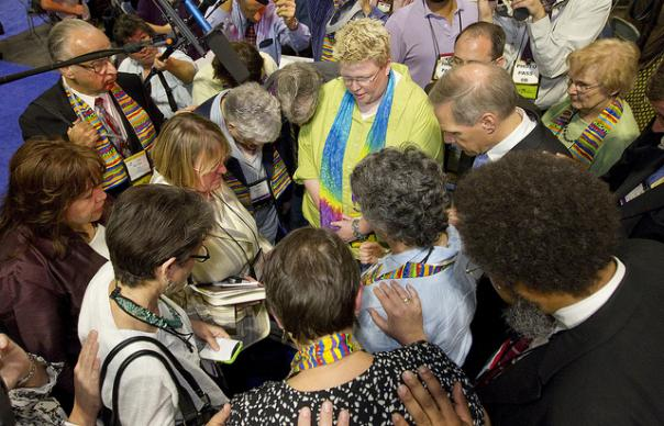 The Rev. Troy Plummer is among in prayer with United Methodist bishops and supporters on the floor of the 2012 United Methodist General Conference in Tampa, Fla. Advocates for greater inclusivity in the church, including DeLong, had occupied the conference's central table following morning votes on the contentious issue. A UMNS photo by Mike DuBose.