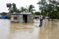 A resident of a low-lying area of Port-au-Prince flees his flooded home taking whatever possessions with him. UN Photo/Logan Abassi