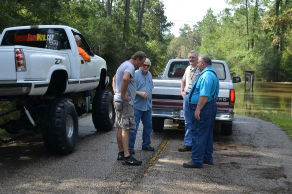 Gene Coumas visits with Milton, Cottrill and Bourque on the flooded road leading to Lee's Landing United Methodist Church. Coumas in his truck (left) rescued several members of the community trapped by floodwaters.