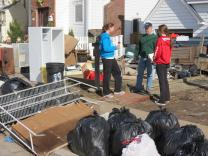Rev. Jeff Wells, in green, checks in with one of his youth group members and her friends in front of the teen's storm-damaged home in Massapequa, N.Y. on November 3.