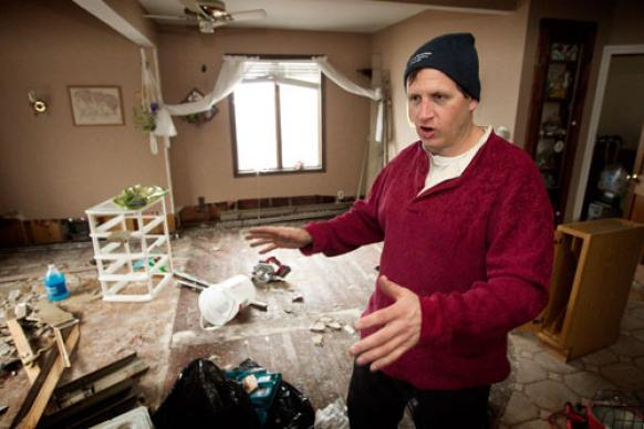 Peter Vasquenz describes damage to his mother's home in the Staten Island borough of New York following Hurricane Sandy. Vasquenz, a firefighter in Brooklyn, had been ripping out waterlogged drywall and flooring. A UMNS photo by Mike DuBose