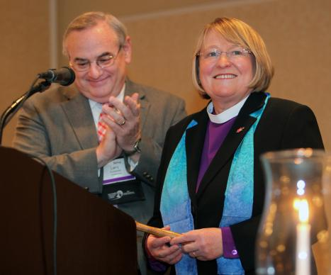 "Bishop Rosemarie Wenner, Council of Bishops president, accepts the gavel from the former council president, Bishop Larry M. Goodpaster, in a ""passing of the gavel"" ceremony April 26 in Tampa, Fla. A UMNS file photo by Kathleen Barry."