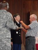 Jim Meeker, Lt. Col. Karen Meeker's father, places shoulderboard showing her new rank. Photo courtesy of Meeker family.
