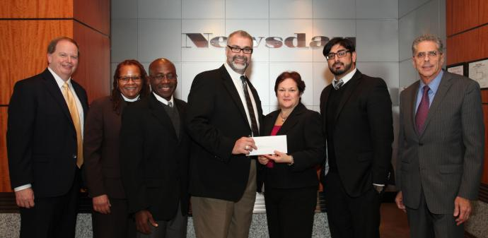UMCOR's Rev. Tom Hazelwood (center) receives a check from Dale Cole, Community Affairs project manager for Newsday. They are flanked by, from left to right, Bill Kohl, Communities Program director, McCormick Foundation; Rev. Adrienne Brewington, Long Island East District Superintendent; Rev. Joseph Ewoodzie, New York Annual Conference Disaster Response coordinator; Kashif Shaikh, program officer, McCormick Foundation; and Paul Fleishman, vice president Public Affairs, Newsday. Courtesy of Newsday
