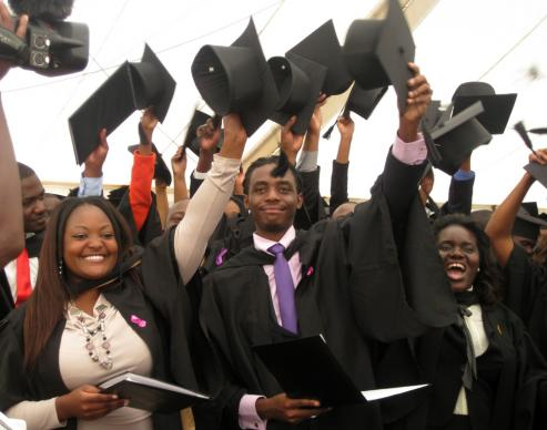 Graduates of the 2013 ceremony at Africa University wave their caps in the air in celebration. Photo courtesy of Africa University
