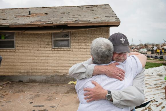 The Rev. Tish Malloy (left) hugs the Rev. Mark Whitley during the cleanup of tornado damage at the home of Trent Steward in Moore, Okla. A UMNS photo by Mike DuBose.