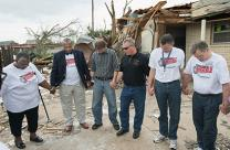 Bishop Robert Hayes Jr., second from left, joins in a prayer at the tornado-damaged home of United Methodist Trent Steward in Moore, Okla. UMNS photo by Mike DuBose.