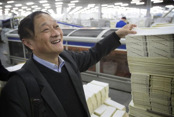 The Rev. Bao Jiayuan looks over stacks of newly-printed Bible pages at the Amity Printing Co. in Nanjing, China. During China's Cultural Revolution, when the practice of religion was forbidden, Bao took comfort in the Bible verses he had memorized as a child. UMNS photos by Mike DuBose.