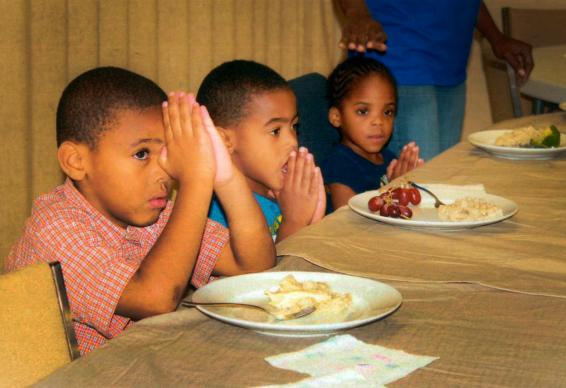 Children pray before dinner. United Methodists comprise 20 percent of all volunteers and congregations among the 182 Family Promise affiliates.