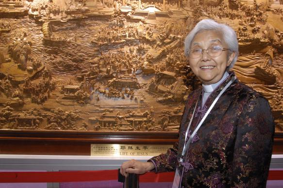 """The Rev. Cao Sheng-jie, president of the China Christian Council, stands next to a giant wood carving that is part of the """"A Lamp to My Feet, A Light to My Path,"""" a Bible ministry exhibition from China.  A UMNS photo by John Goodwin."""