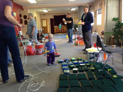 Members of Highlands United Methodist Church in Denver assemble cleaning buckets for those affected by the Colorado floods, while toddler Emma, daughter of two of the volunteers (not pictured) plays amid the cleaning supplies. A UMNS photo by Bradley Laurvick.