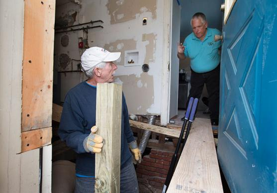 Lou Strugala (right) checks in with volunteer Sid Riddick as he repairs damage from Hurricane Sandy at a home in Atlantic City, N.J. Riddick was part of a volunteer team from Matthews (N.C.) United Methodist Church. Strugala is director of construction for A Future With Hope, a long-term recovery program of the Greater New Jersey Conference of The United Methodist Church.
