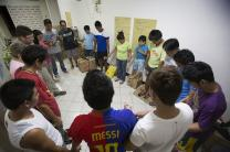 Staff members and volunteers for the United Methodist Committee on Relief pray in their Manila office after preparing bags of relief supplies for transport to survivors of Typhoon Haiyan in the Philippines. UMNS photos by Mike DuBose