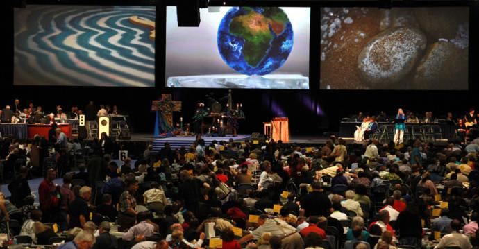 A communion wafer is painted with the world and projected on the screen at the 2012 United Methodist General Conference. A UMNS photo by Kathleen S. Barry.