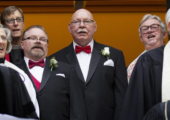 Richard Taylor (left, center) and William Gatewood sing a hymn with clergy and faith leaders after their wedding at Arch Street United Methodist Church. At left rear is the Rev. Robin Hynicka, senior pastor. At right is the Rev. Herbert Snyder, who served Arch Street before his retirement.