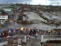 Tacloban city residents queue for relief goods outside the rubble of Daniel Romualdez Tacloban airport. Photo by Julliane Love De Jesus.