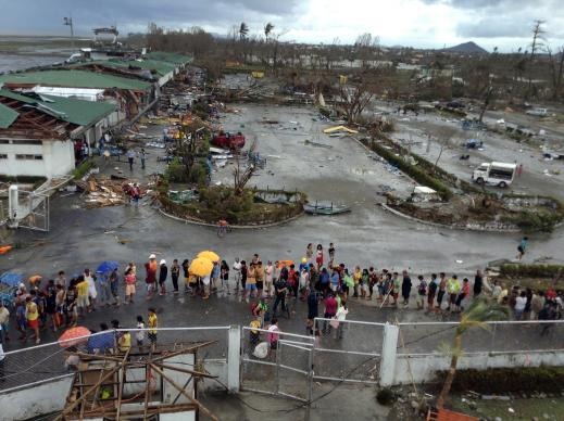Tacloban city residents queue for relief goods outside the rubble of Daniel Romualdez Tacloban airport. Photo by Julliane Love De Jesus.