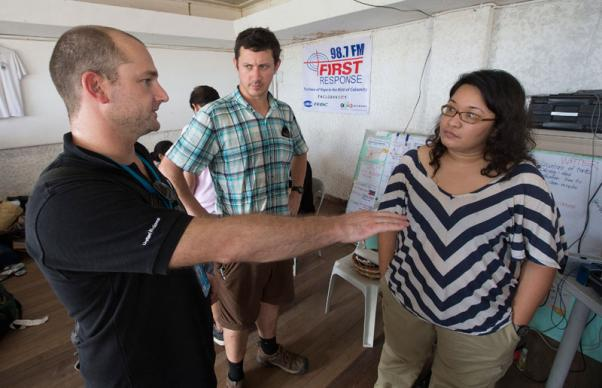 Stewart Davies (left) of the United Nations and Clark Ritchie (center) of Inveneo visit with Maggie Yrasuegui of FEBC Radio, which is providing information for survivors of Typhoon Haiyan in Tacloban.