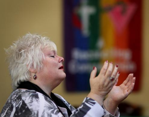 A tearful Judi Grimes prays in support of Rev. Frank Schaefer during a vigil held Monday, Nov. 18, at Edgehill United Methodist Church in Nashville, Tenn. A UMNS photo by Kathleen S. Barry.
