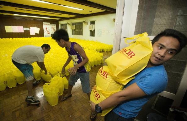 Volunteer Vincent Salazar (right) helps a team with the United Methodist Committee on Relief in Manila as they load bags of relief supplies for survivors of Typhoon Haiyan in the Philippines. UMNS photso by Mike DuBose.