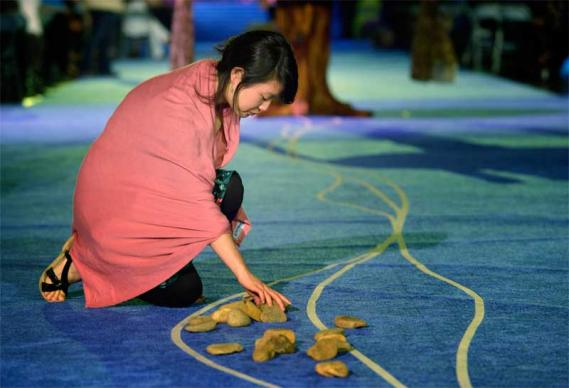 "A delegate picks up a stone in the center aisle during an April 27 ""Act of Repentance toward Healing Relationships with Indigenous Peoples"" at the 2012 United Methodist General Conference in Tampa, Florida."