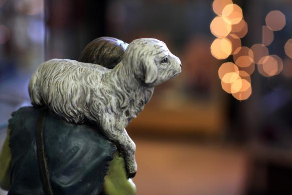 A nativity figure of a shepherd holds a young lamb. Photo by Kathleen Barry, United Methodist News Service.