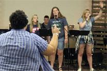Kaitlin Kendel from Abilene Emanuel UMC leads a group practicing to lead worship at the Great Plains Annual Conference session during the recent Amp It Up! music camp at Southwestern College. Photo by David Burke