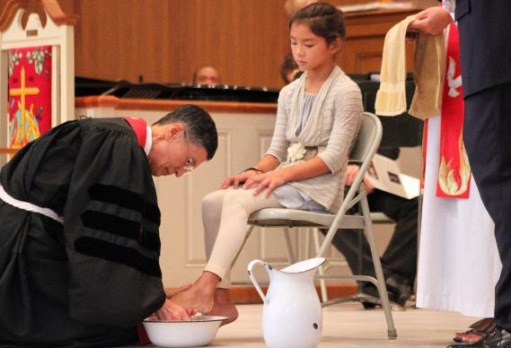 Bishop Young Jin Cho washes the feet of a student during his installation in 2012. Photo by Neill Caldwell.