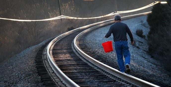 Man walking down railroad tracks carrying bucket. Photo illustration by Kathleen Barry, United Methodist Communications.