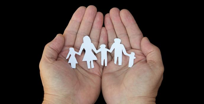 Hands hold paper dolls. Photo illustration courtesy of United Methodist Communications.
