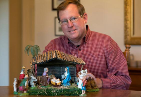 Gilbert Lovell of Franklin, Tenn., poses with a Nativity set made by his mother. Photo by Mike DuBose, United Methodist Communications.