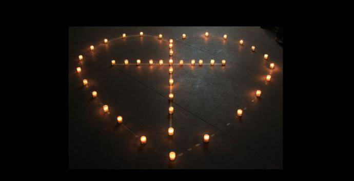 Lit candles form the shape of a cross inside of a heart. Photo by Wingchi Poon, courtesy Flickr.